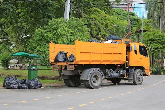 Camion à ordures avec chargement des déchets dans le jardin du parc.