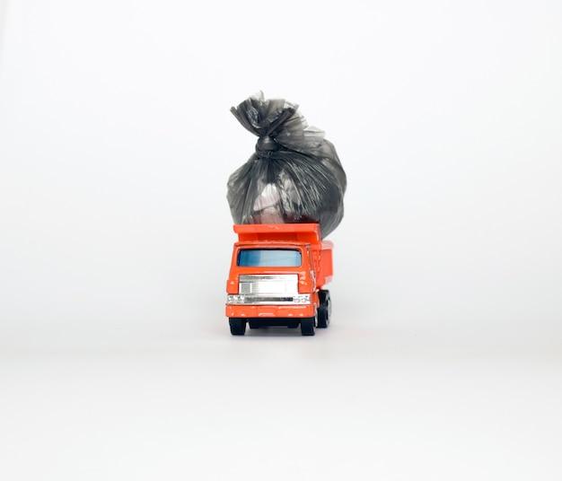 Camion à ordures jouet avec des sacs à ordures isolé sur fond blanc