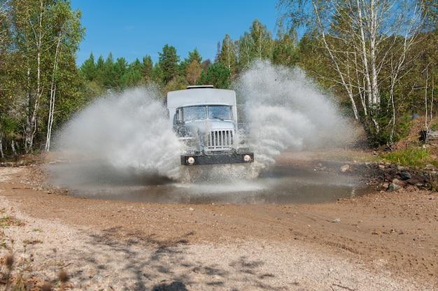 Un camion passe dans une flaque