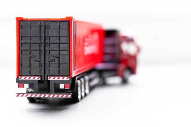 Camion porte-conteneur mise au point sélective sur fond blanc, parking de camion-conteneur remorque à l'entrepôt, société de transport et de logistique commerciale mondiale.