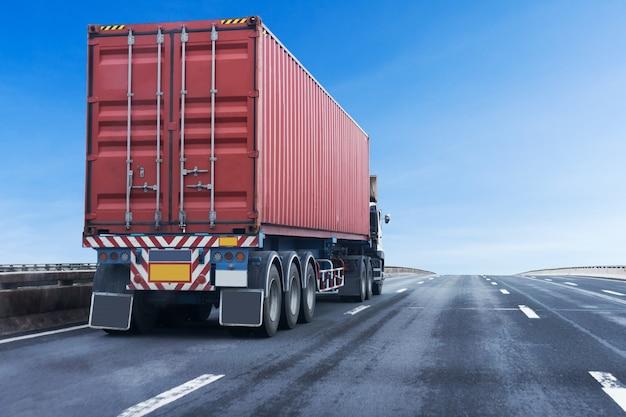 Camion sur la route de l'autoroute avec conteneur rouge, transport logistique sur l'autoroute asphaltée