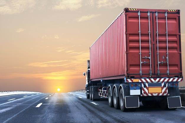 Camion sur la route de l'autoroute avec un conteneur rouge
