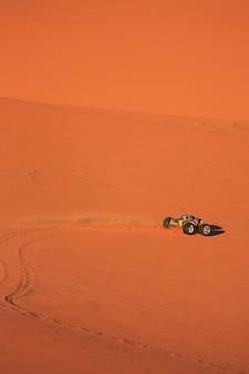 Camion télécommandé conduisant sur des dunes de sable