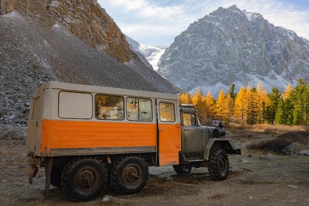 Le camion tout-terrain se dresse sur fond de mélèzes jaunes des montagnes