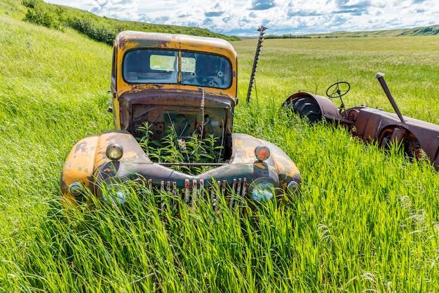 Camion et tracteur jaune antique abandonné dans les hautes herbes