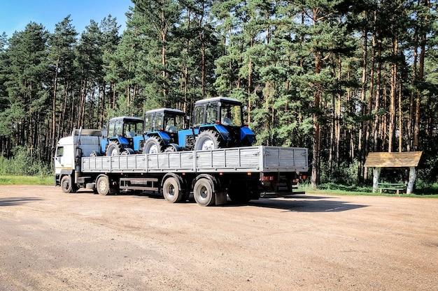 Camion avec tracteurs dans la remorque sur la route.