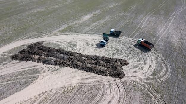 Les camions transportent dans le domaine des engrais organiques avec un drone de photographie aérienne.