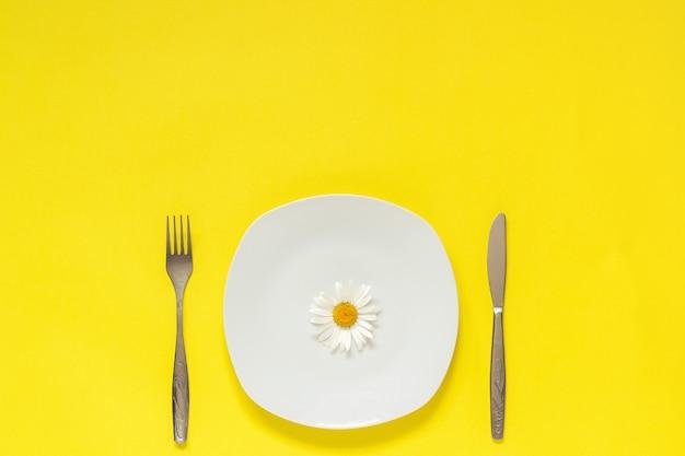 Camomille une fleur sur une assiette, couteau à fourchette à couverts concept végétarien alimentation saine ou anorexie