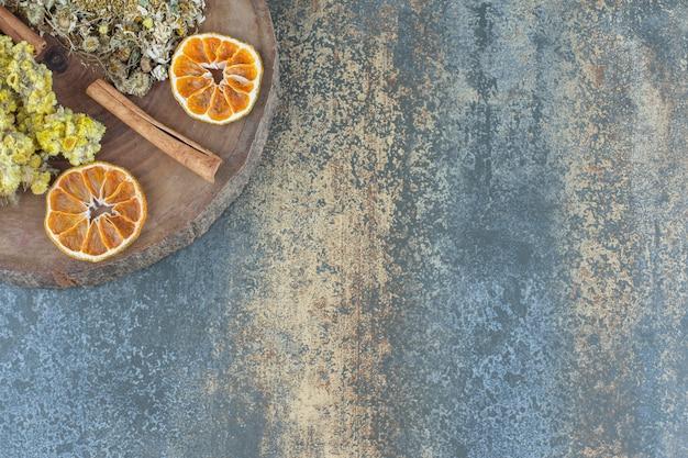 Camomille séchée et chrysanthème sur morceau de bois.