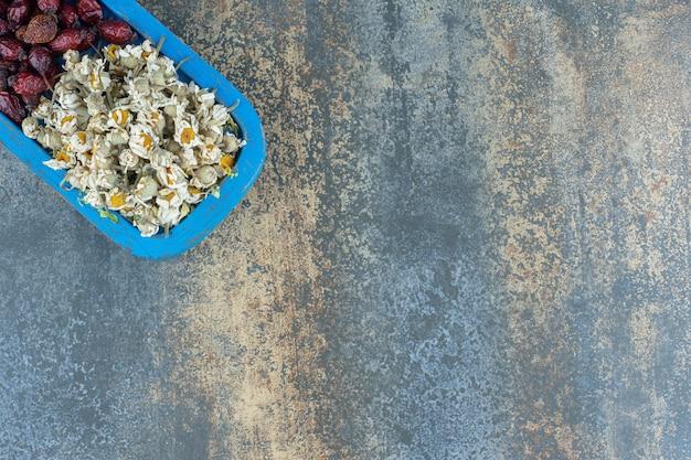 Camomille séchée et églantier sur plaque bleue.