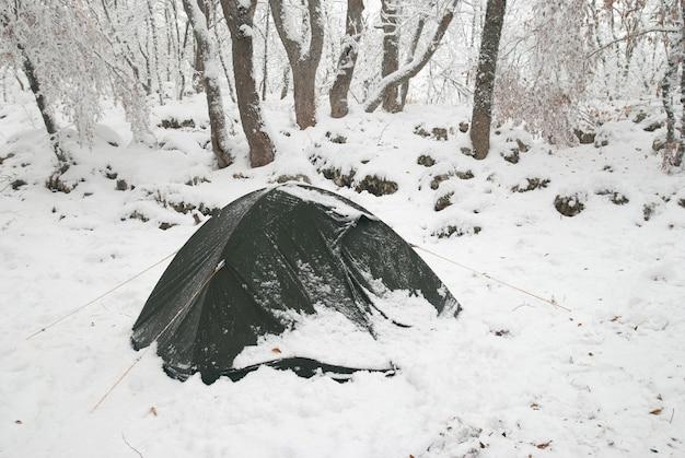 Camp de tentes d'hiver dans la forêt de neige