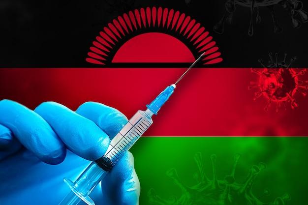 Campagne de vaccination du malawi covid19 la main dans un gant en caoutchouc bleu tient une seringue devant le drapeau