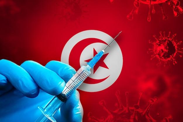 Campagne de vaccination de tunisie covid19 la main dans un gant en caoutchouc bleu tient une seringue devant le drapeau