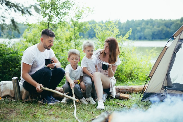 Camping au bord du lac dans les bois. famille heureuse papa maman et petits enfants assis au coin du feu et tente dans la nature. passer du temps libre ensemble en vacances. en plein air. parents avec enfants tenant une tasse