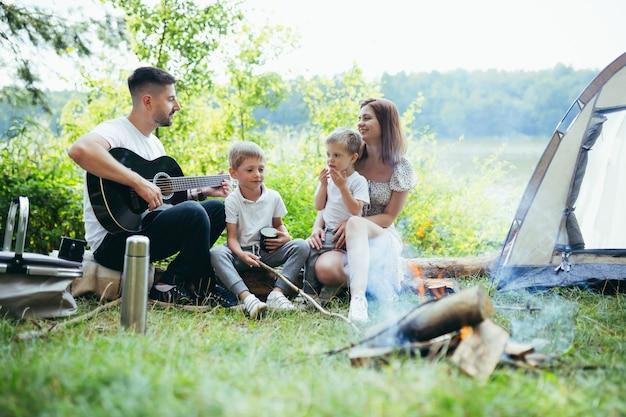 Camping au bord du lac dans les bois. papa de famille heureux maman et petits enfants assis au coin du feu et tente dans la nature. passer du temps libre ensemble en vacances. en plein air. parents avec enfants. père jouant de la guitare. camp
