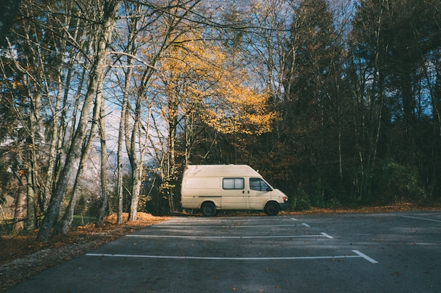 Camping-car garé sur le parking dans la forêt. concept de camping et d'aventure