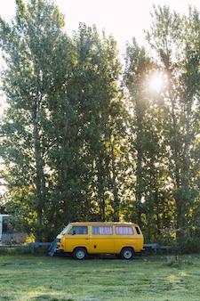 Camping-car jaune garé à côté de grands arbres dans un camping