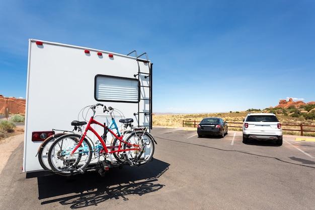 Camping-car avec vélos sur route goudronnée. montagnes rocheuses en arrière-plan.