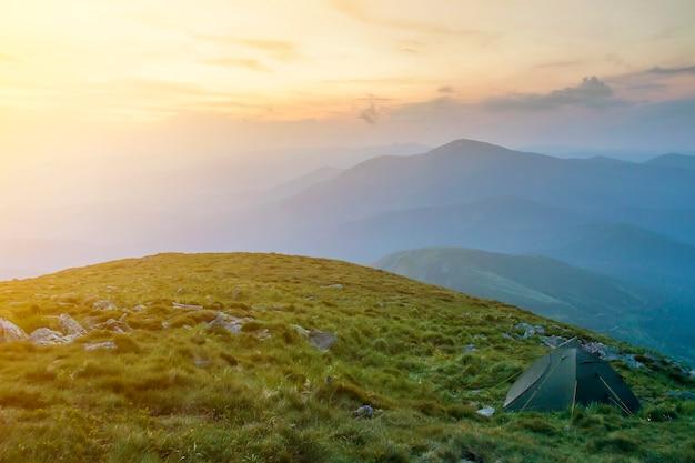 Camping d'été dans les montagnes à l'aube. tente touristique sur une colline herbeuse ronde sur des montagnes bleues brumeuses éloignées sous le ciel rose avant le lever ou le coucher du soleil. tourisme, randonnée et beauté du concept de la nature.