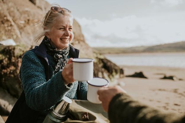 Camping-femme senior tenant une tasse à café avec espace design