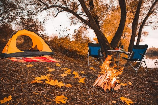 Camping lieu d'automne avec feu de joie et chaises portables sans personnes.