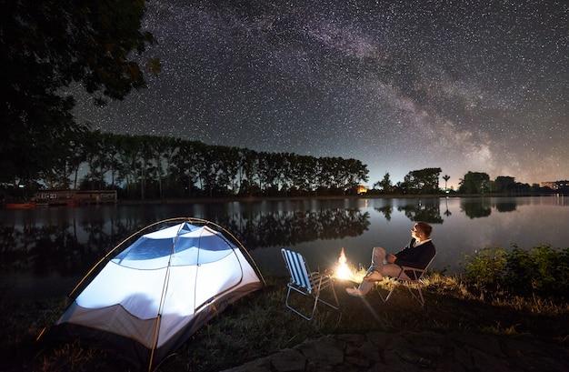 Camping de nuit au bord du lac près d'un feu de camp