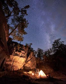 Camping de nuit. jeune couple de touristes, homme et femme debout près d'une petite tente éclairée par un feu brûlant