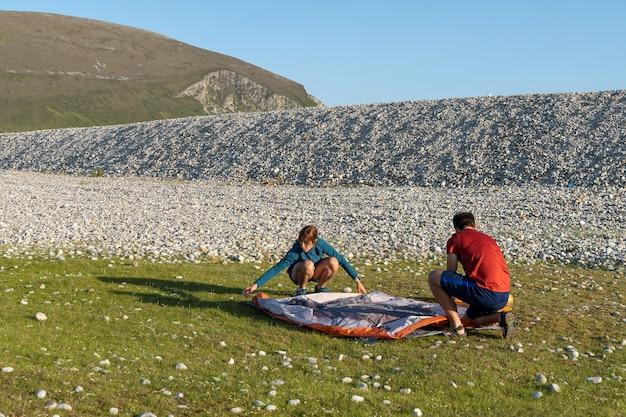 Camping personnes couple de style de vie en plein air mettant en place une tente dans la nature plage rocheuse