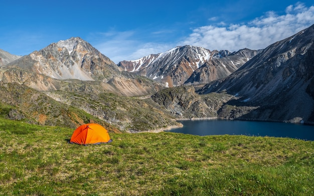 Camping sur un plateau verdoyant d'altitude en été. vue panoramique sur un lac de montagne bleu dans l'altaï avec tente sur le rivage. beau lac turquoise.