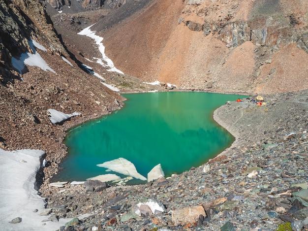 Camping près d'un lac de montagne glaciaire, vue lointaine. camp d'alpinisme au lac bleu. chaîne de montagnes d'aktru, altaï.