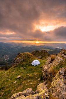 Camping sauvage au sommet d'une montagne au coucher du soleil, dormir en plein air après le long trek en montagne
