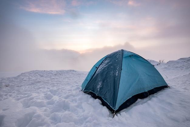 Camping tente bleue sur la colline enneigée dans le brouillard