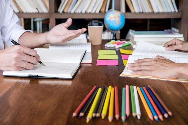 Le campus étudiant ou ses camarades de classe aident un ami à se remettre un cahier de travail et à apprendre à faire du tutorat en classe