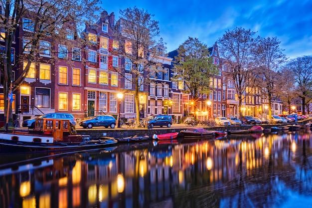 Canal d'amsterdam, bateaux et maisons médiévales dans la soirée