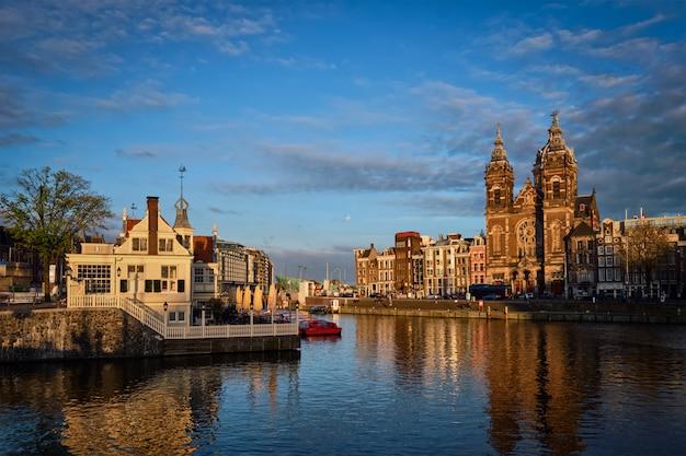 Canal d'amsterdam et église saint-nicolas au coucher du soleil