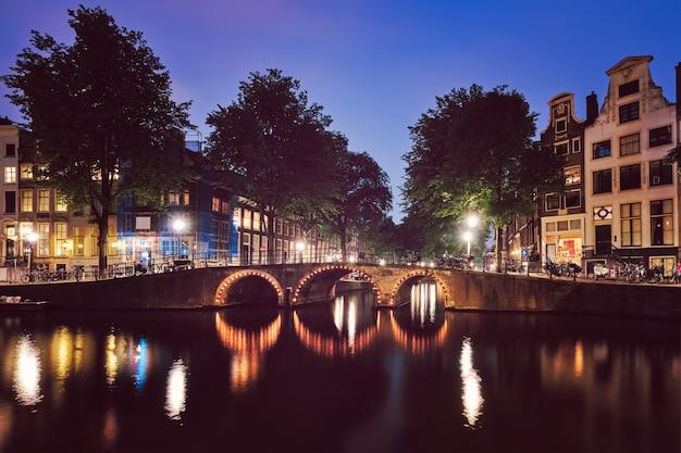 Canal d'amsterdam, pont et maisons médiévales dans la soirée