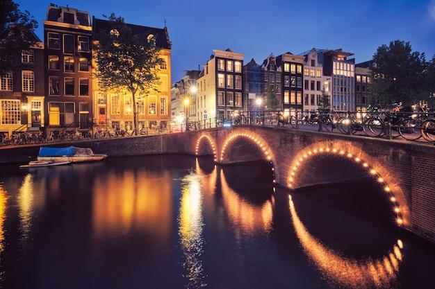 Canal d'amsterdam, pont et maisons médiévales en soirée