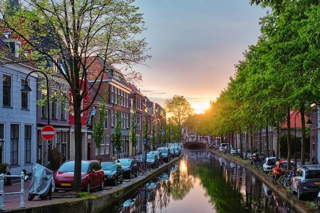Canal de delt avec de vieilles maisons et voitures garées le long du coucher du soleil