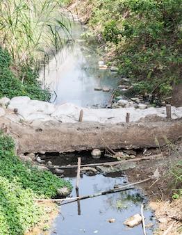Canal d'eaux usées avec petit barrage en sacs de sable