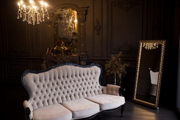 Canapé beige antique dans une pièce sombre avec un miroir vintage.