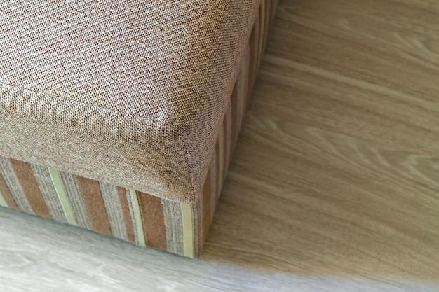 Canapé beige moderne texturé dans le salon sur parquet stratifié en bois