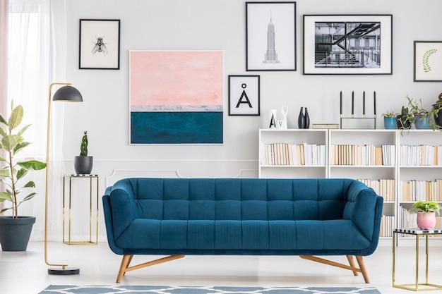 Canapé bleu confortable situé à l'intérieur d'un salon blanc avec étagère et peintures