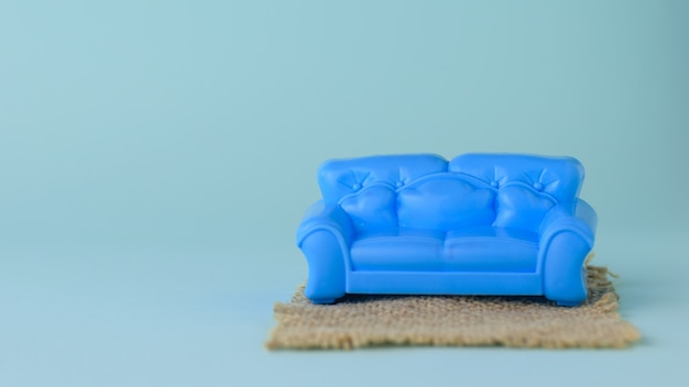 Canapé bleu sur tapis sur fond bleu. un échantillon de beaux meubles pour la maison. minimaliste.
