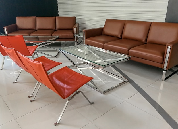Canapé brun vide et table en verre et chaise orange dans le salon au bureau d'affaires., concept de bureau intérieur., concept en attente.
