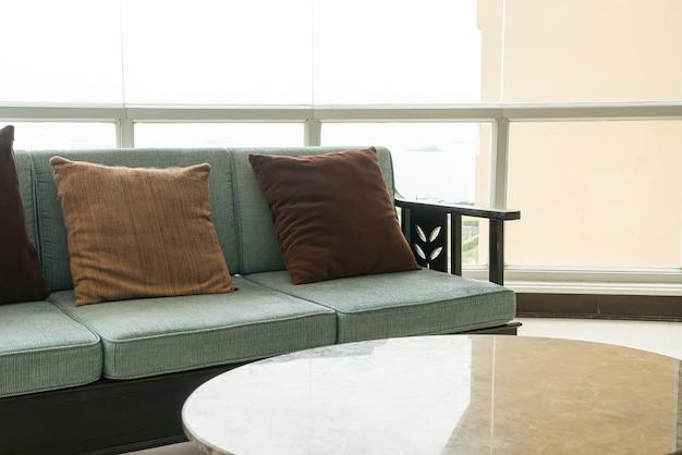 Canapé et chaise vides avec décoration d'oreillers dans une chambre