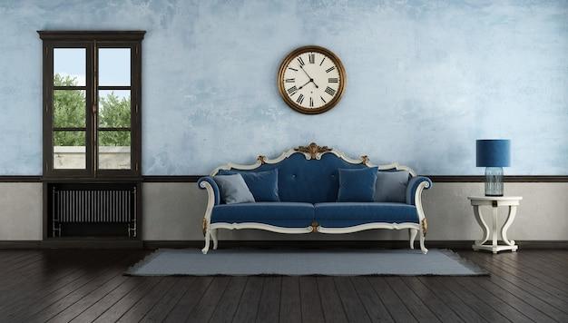Canapé classique bleu dans une ancienne pièce avec un vieux radiateur sous des fenêtres en bois