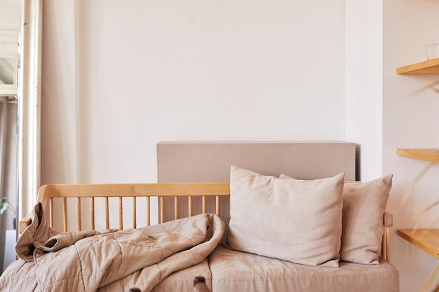 Canapé confortable avec coussins et couverture contre mur blanc