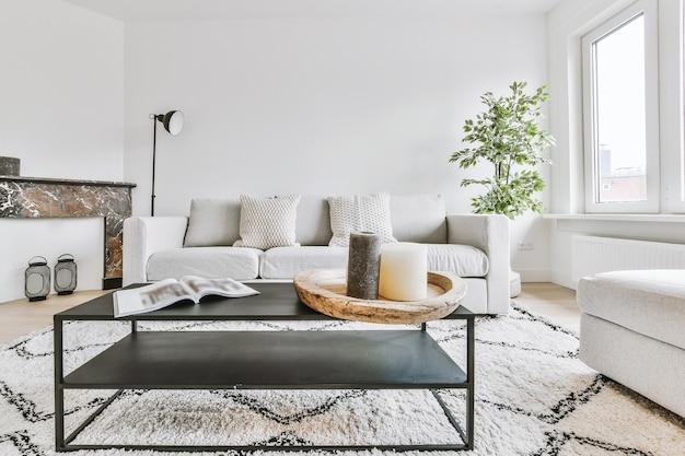 Canapé confortable avec coussins situés sur un tapis près de la table dans un salon lumineux avec fenêtre et porte dans un appartement moderne