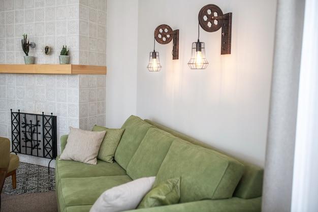 Canapé confortable en velours vert olive avec plusieurs coussins jouxtant un mur de cheminée à motifs en céramique blanche dans un salon vide
