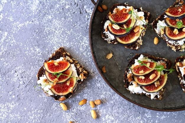 Canape, crostini ou bruschettas aux figues fraîches, pain, fromage à la crème, miel